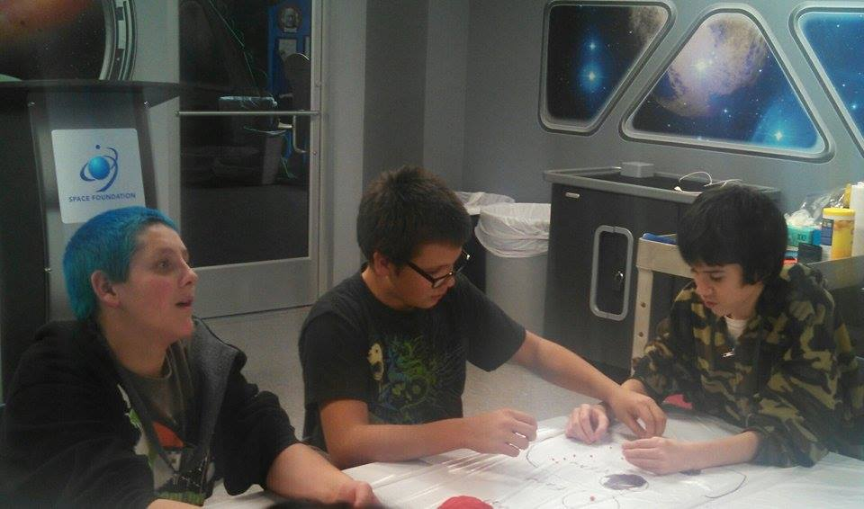 Gardner School students (left to right); Dominic Vigil, Jason Jardine and Jason Reichmann making a scale model of the solar system at the Space Foundation Discovery Center in Colorado Springs.